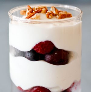 Glass layered with fruit, Greek yogurt, and chopped pecans