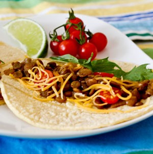 Tortillas topped with cooked lentils, halved cherry tomatoes, parsley, and lime wedge
