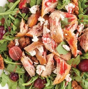 Shredded pork bites and walnuts over salad