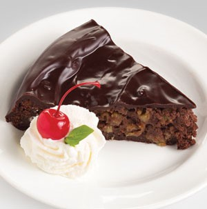 Slice of chocolate cherry cake on a white plate served with a side of whipped topping, a maraschino cherry and a mint leaf