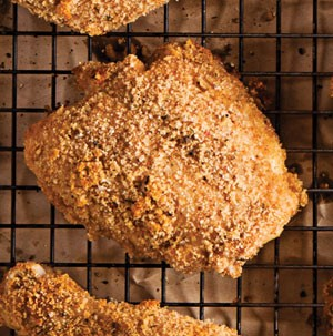 Breaded chicken on a wire rack over parchment paper