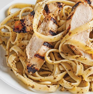 White plate of pesto pasta topped with grilled strips of chicken
