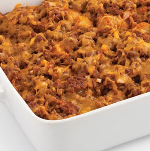 White casserole dish filled with tator tots and ground beef covered in melted cheddar cheese