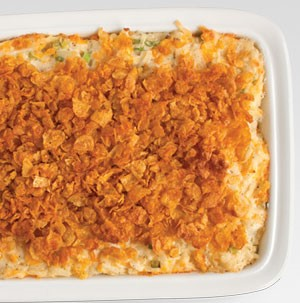 White casserole dish filled with potato casserole and flaked corn cereal on top
