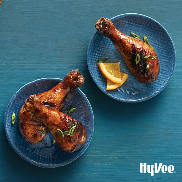 Small blue plates of chicken drumsticks covered in plum sauce and green onions