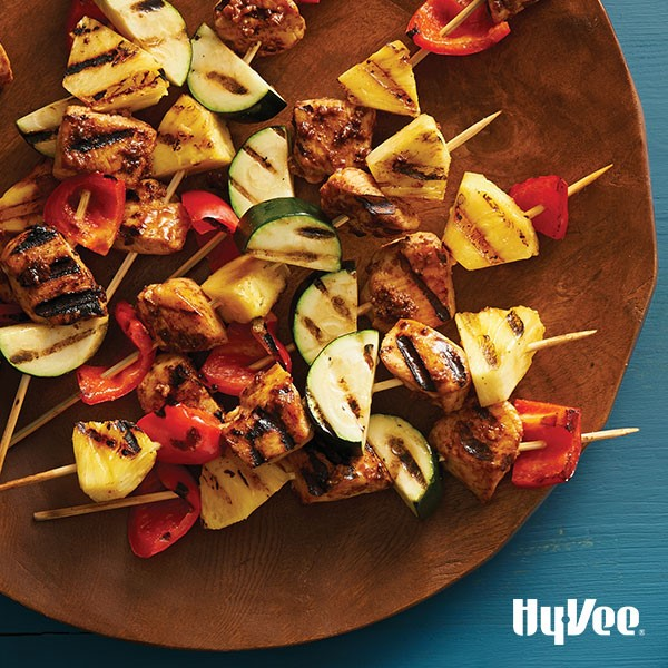 Wooden platter of chicken and vegetable kabobs seasoned in a spiced bacon rub