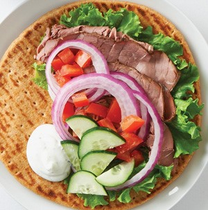 Flat pita topped with chopped tomatoes, cucumbers, sliced red onions, shaved deli meat, and lettuce leaves