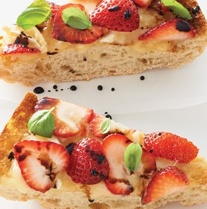Toasted ciabatta bread slices topped with brie, strawberry slices, balsamic and basil
