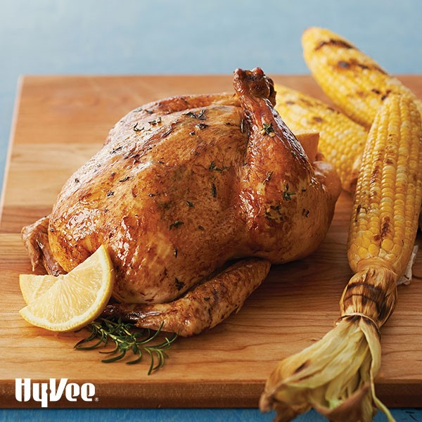Whole chicken on a wooden cutting board with grilled corn, fresh rosemary, and lemon wedges