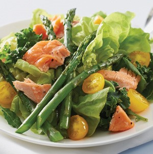 Mixed green salad topped with flaked cooked salmon, halved cherry tomatoes, and asparagus spears