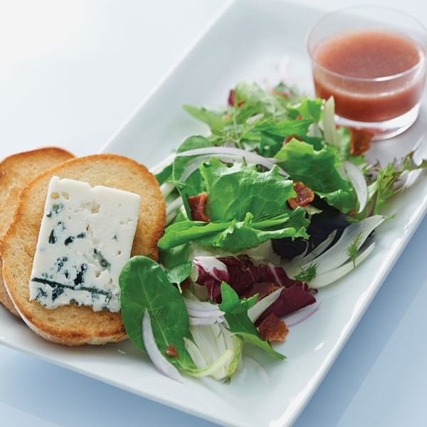 Plate of fennel salad served with a side of vinaigrette and two bread slices topped with cheese