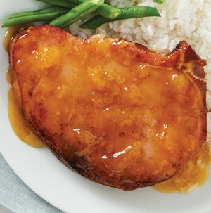 Plate of pork chops covered in peach glaze, served with white rice and beans