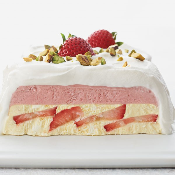 Strawberry cream filling stacked with berry mixture and whipped cream topping and garnished with strawberries and pistachios