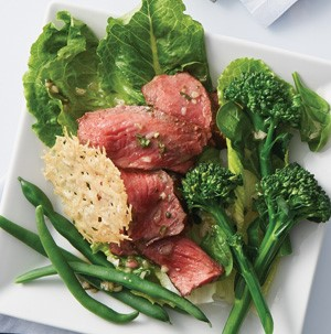 Green beans, sliced steak, broccolini , and parmesan chip on a white square plate