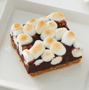 White plate with a toffee bar, topped with golden-brown mini marshmallows