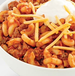 Elbow macaroni with red meat sauce topped with shredded cheese and sour cream