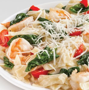Creamy pasta and shrimp with halved cherry tomatoes, spinach, and shredded cheese