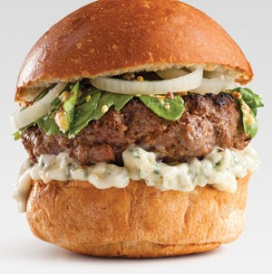 Bun topped with blue cheese spread, burger patty, greens, and yellow onions