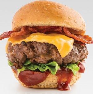 Cheeseburger patty with lettuce, BBQ sauce and bacon sandwiched between a slider bun