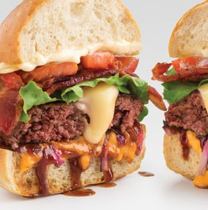 Bun topped with melted cheese, burger patty, sliced bacon, and sliced tomatoes