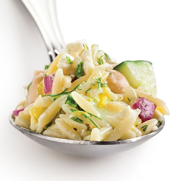 Spoon filled with orzo, red onion, chopped cucumber, and chickpeas