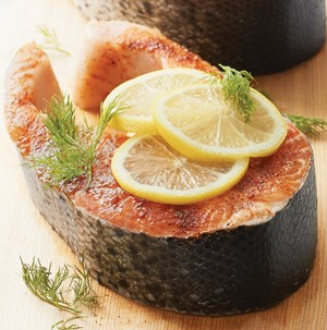 Seasoned salmon steak on a wooden plank, garnished with lemon slices and fresh dill sprigs