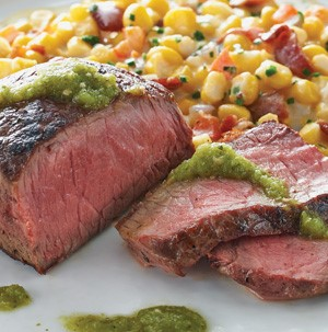 Salsa verde topped sliced steak with a side of creamed corn