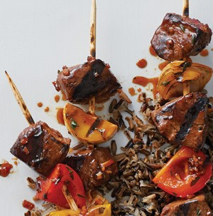 Cubed grilled steak on skewers with onions and bell peppers with rice in background