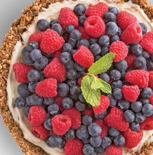 Tort topped with creamy filling, fresh blueberries and raspberries, and a fresh mint leaf for garnish