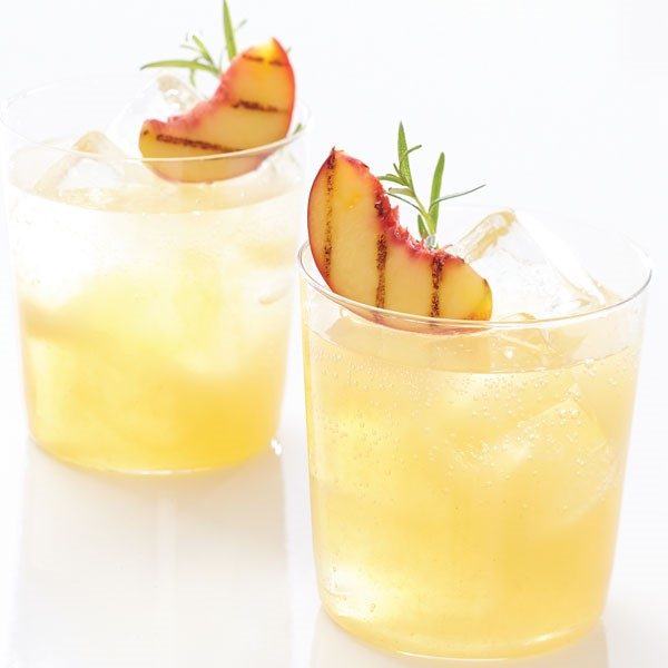 Two glasses of iced spritzer, garnished with grilled peaches and sprigs of rosemary