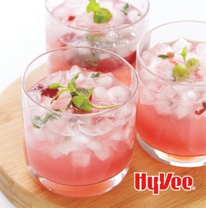 Glasses of cherry mojitos garnished with cherries and mint