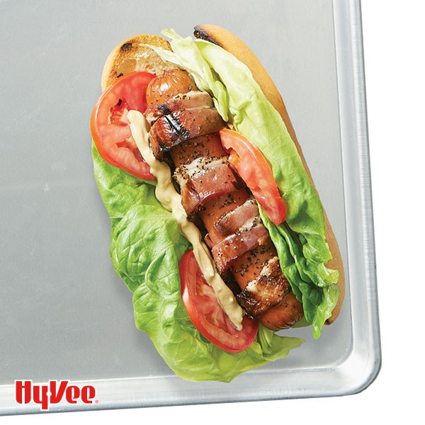 Grilled hot dog and bun topped with lettuce, tomatoes, bacon and mayo