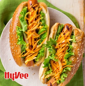 Two grilled hot dogs topped with spicy mayo, onion and carrots and placed in sesame seed hoagies