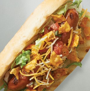 Hot dog bun with grilled hot dog, shredded cheese and lettuce and broken corn chips