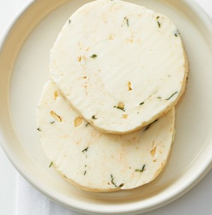 Circular slices of compound butter on a white dish