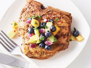 Seasoned pork chop topped with fruit salsa on a white plate with a fork and knife