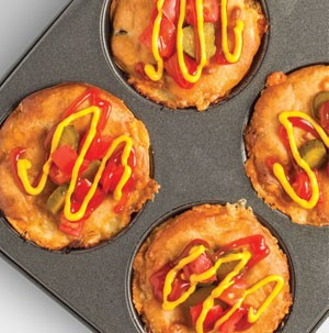 Cheeseburger pies in muffin tin with diced vegetables and drizzled with yellow mustard and ketchup