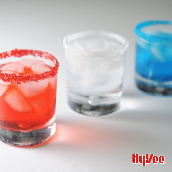 Three sugar-rimmed glasses filled with red, white and blue liquid