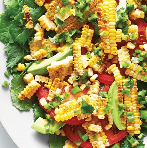 Sliced corn on the cob mixed with green peppers, sliced avocados, sliced tomatoes and mixed greens