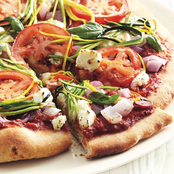 Thin crust pizza topped with crumbled cheese, thinly sliced zucchini, diced red tomatoes, and sliced heirloom tomatoes