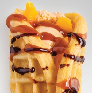 Waffle wrapping mango strips and ice cream and drizzled with caramel and chocolate sauce