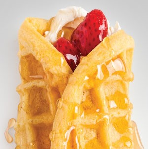 Cream cheese and strawberries wrapped in a waffle and drizzled with honey