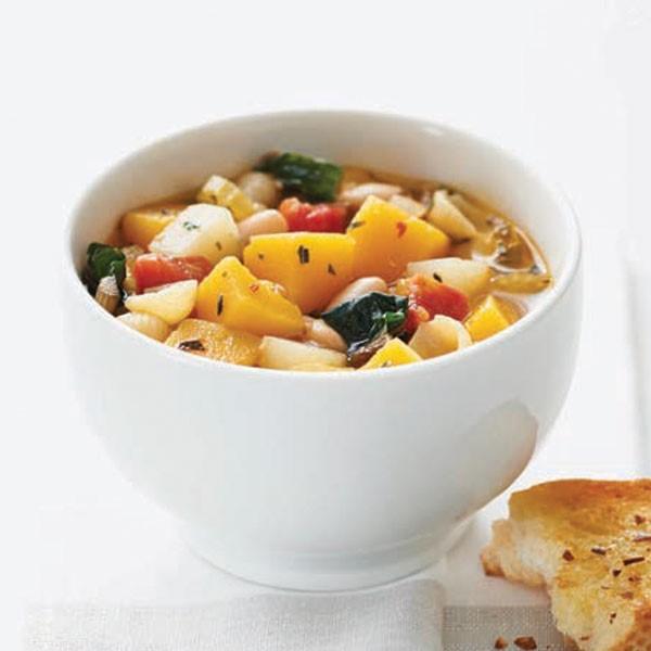 Bowl of vegetable soup next to slice of garlic bruschetta