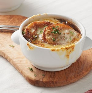 White bowl of french onion soup on a wooden plank