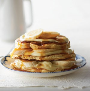 Stack of banana cream pancakes topped with syrup and fresh bananas on a blue-and-white plate