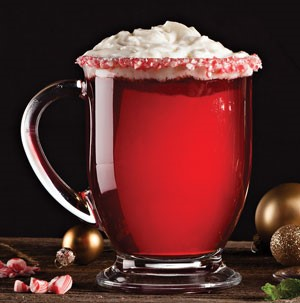 Glass mug filled with red poinsettia drink with whipped topping for garnish