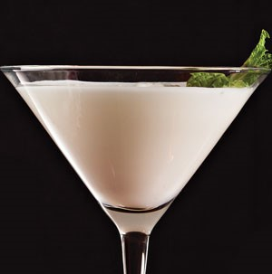White martini in glass garnished with fresh mint leaves