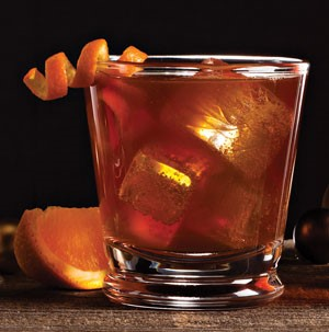 Glass filled with ice cubes, maple ale, spice, and garnished with an orange peel