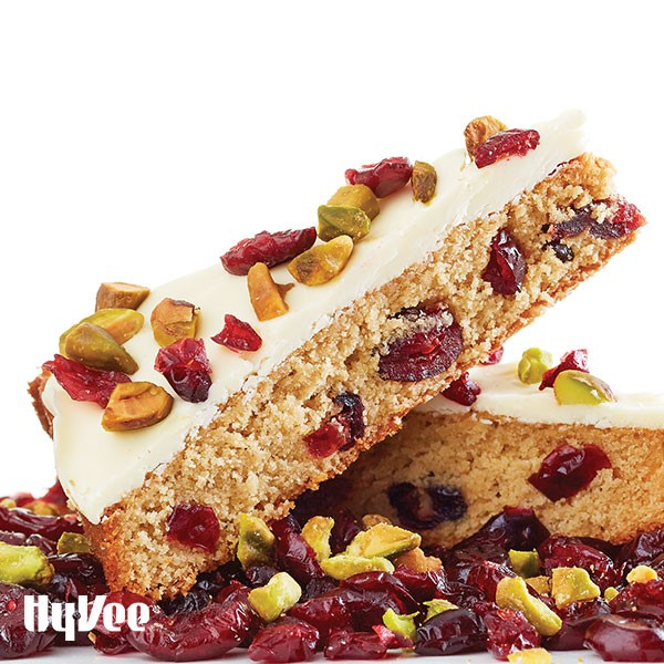 Blond brownies filled with dried cranberries and topped with white frosting, additional dried cranberries, and shelled chopped pistachios