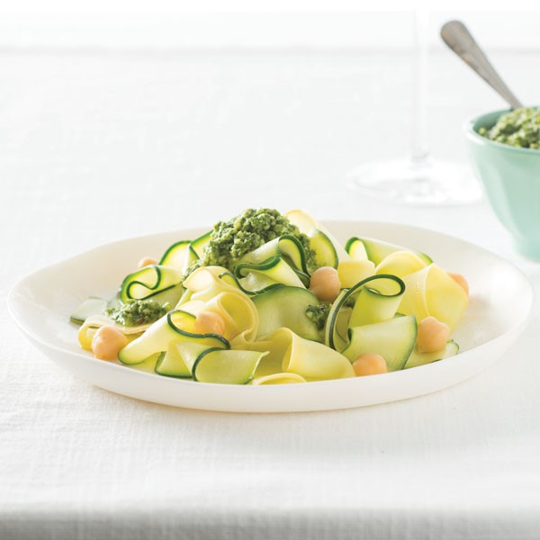 Ribbons of zucchini noodles topped with garbanzo beans and pesto